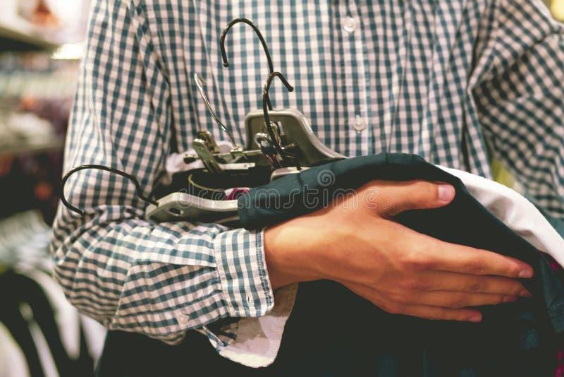 Ciérrese encima de la mano que sostiene el manojo de nueva ropa para comprar en la tienda, un concepto de la venta de las compras fotografía de archivo