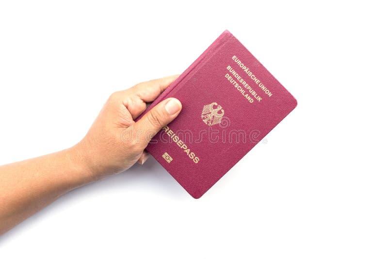 Ciérrese encima de la mano que sostiene el pasaporte alemán aislado en blanco fotografía de archivo