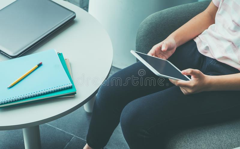Ciérrese encima de la mano de la sentada de la muchacha y toque la pantalla en blanco de la tableta c imagen de archivo libre de regalías