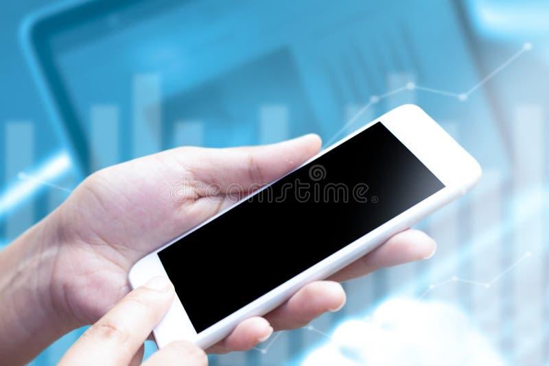 Ciérrese encima de la mano usando el teléfono móvil con la exhibición en blanco en el fondo del ordenador portátil y del gráfico  imágenes de archivo libres de regalías