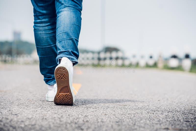 Ciérrese encima de la mezclilla del desgaste de mujer y de la zapatilla de deporte blanca que caminan adelante en hola fotos de archivo libres de regalías