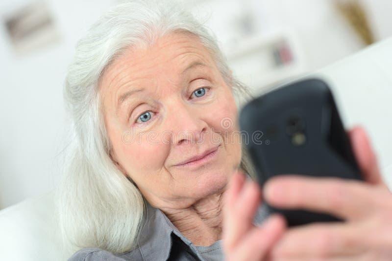 Ciérrese encima de la mujer envejecida centro que usa el teléfono móvil fotografía de archivo