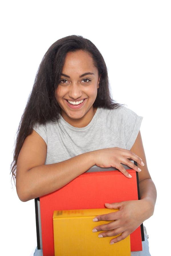 Ciérrese encima de la mujer joven feliz que se inclina en sus libros fotografía de archivo