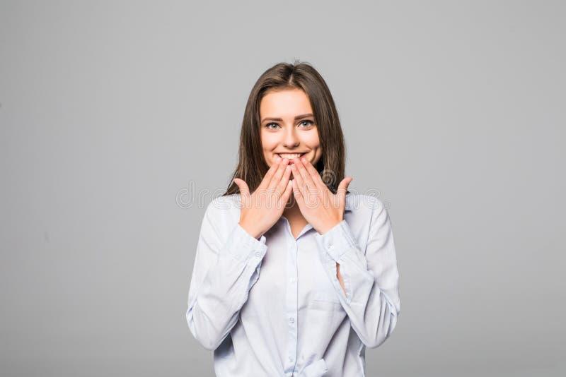 Ciérrese encima de la mujer joven feliz que sonríe en la cámara mientras que cubre su boca con su mano contra Gray Background fotos de archivo libres de regalías