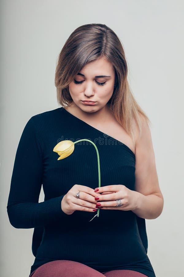Ciérrese encima de la mujer joven triste que detiene a Rose Flower While Looking muerta en la cámara fotos de archivo libres de regalías