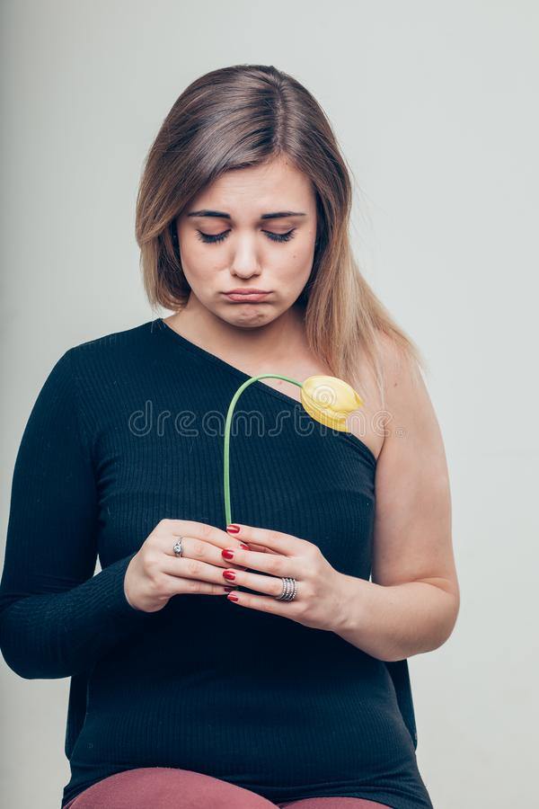 Ciérrese encima de la mujer joven triste que detiene a Rose Flower While Looking muerta en la cámara imagenes de archivo
