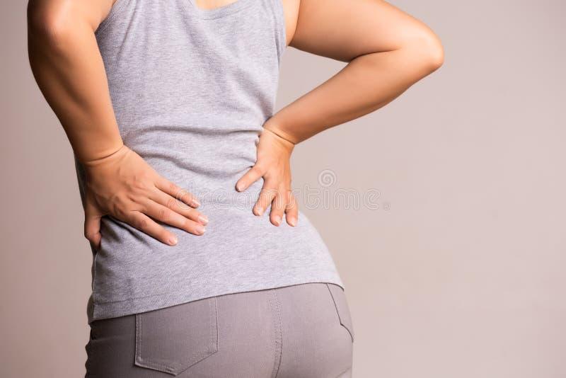 Ciérrese encima de la mujer que tiene dolor en parte posterior herida Atención sanitaria y concepto del dolor de espalda imagen de archivo