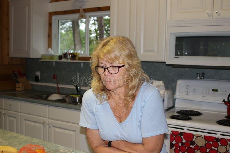Ciérrese encima de la mujer rubia envejecida centro pensativo, sentándose en la sala de estar y mirando para arriba con las manos fotos de archivo libres de regalías