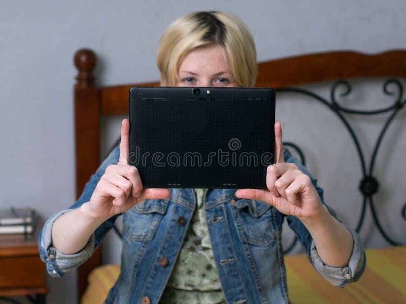 Ciérrese encima de la mujer rubia joven que celebra una tableta y una sonrisa foto de archivo libre de regalías