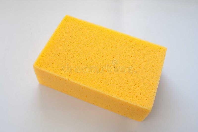 Ciérrese encima de la nueva esponja amarilla aislada en el fondo blanco foto de archivo