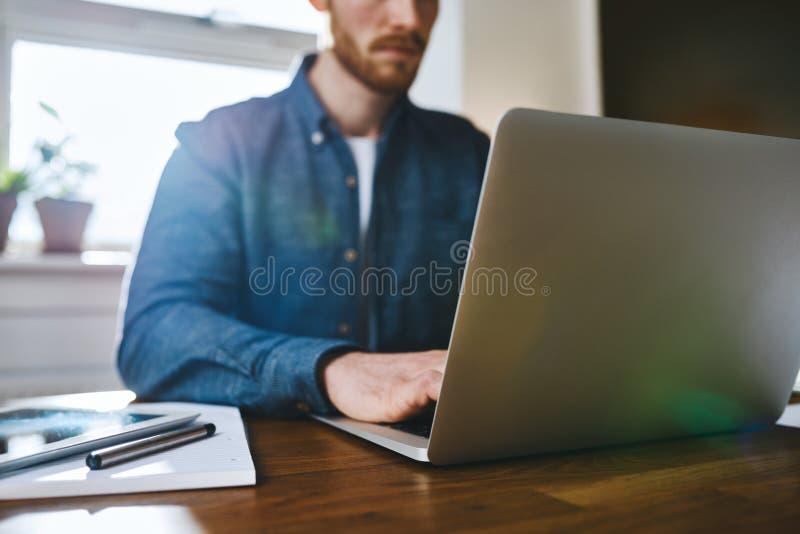 Ciérrese encima de la opinión el hombre que trabaja en el ordenador portátil fotografía de archivo