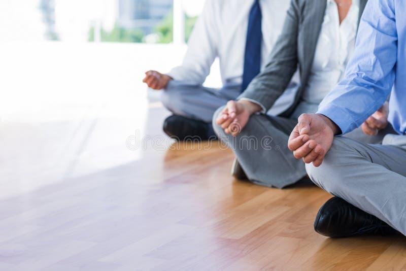 Ciérrese encima de la opinión los hombres de negocios que hacen yoga foto de archivo libre de regalías