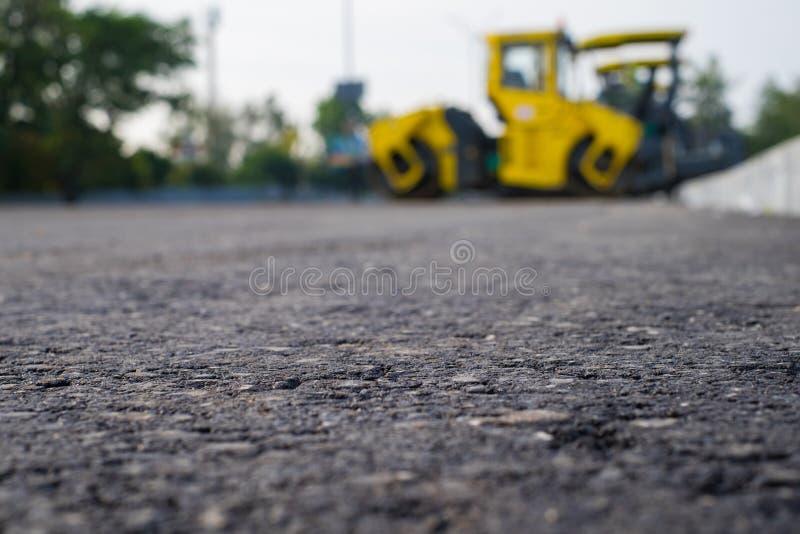 Ciérrese encima de la opinión sobre la nueva carretera de asfalto en la cual el rodillo de camino está funcionando Emplazamiento  fotos de archivo libres de regalías