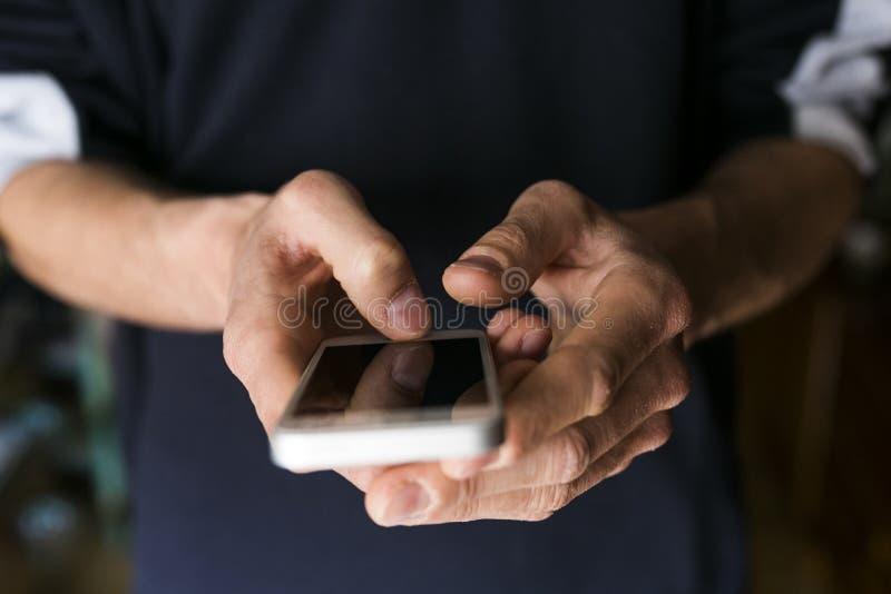 Ciérrese encima de la opinión un hombre que sostiene un teléfono elegante Ropa ocasional fotografía de archivo libre de regalías