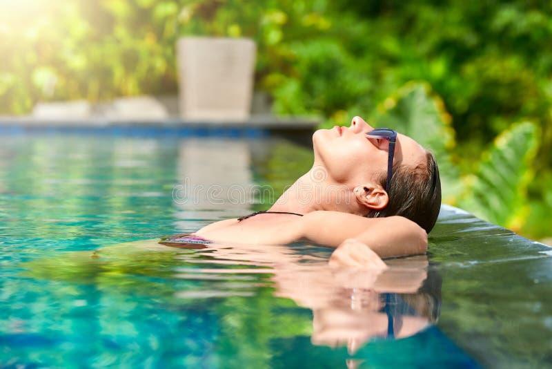 Ciérrese encima de la opinión una mujer joven atractiva que se relaja en un ` s s del balneario imagen de archivo