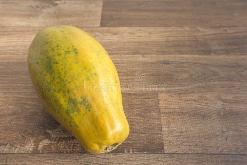 Ciérrese encima de la papaya entera en fondo de madera imágenes de archivo libres de regalías
