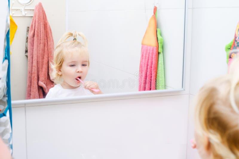 Ciérrese encima de la pequeña hija del niño que cepilla sus dientes y que mira en el espejo en el cuarto de baño Reflexión en el  imagen de archivo libre de regalías