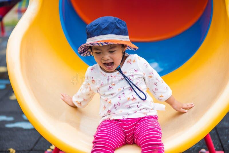 Ciérrese encima de la pequeña muchacha linda feliz que tiene la diversión y desplazamiento imagenes de archivo