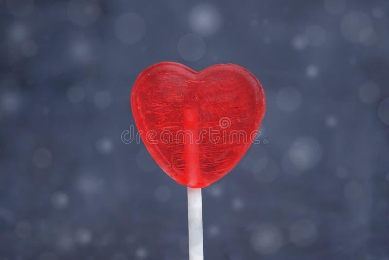 Ciérrese encima de la piruleta roja de la corazón-forma aislada en el fondo azul de Bokeh Concepto del día del ` s del amor y de  imagen de archivo