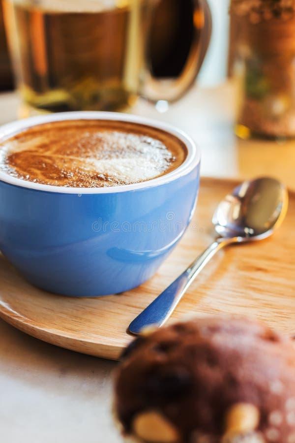 Ciérrese encima de la taza de café con vapor en la tabla en café fotos de archivo