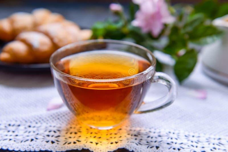 Ciérrese encima de la taza de cristal de té caliente en la servilleta del vintage con los cruasanes y las flores color de rosa de fotos de archivo libres de regalías