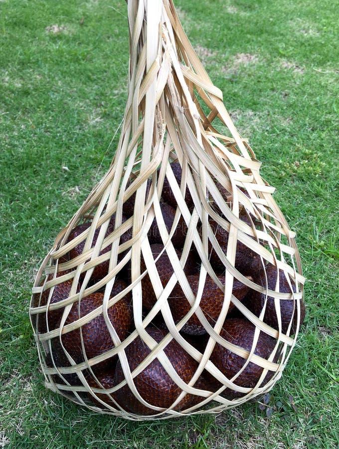 Ciérrese encima de la vista de la fruta de la serpiente (Salak) en un bambú tradicional fotos de archivo