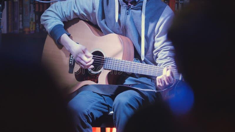 Ciérrese encima de la vista de la guitarra acústica de los juegos del guitarrista en club de noche fotos de archivo libres de regalías
