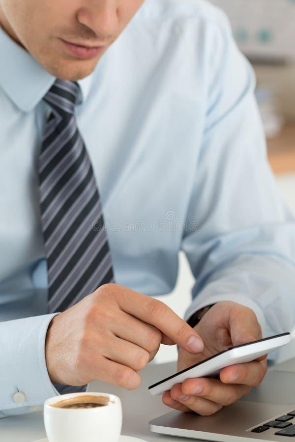 Ciérrese encima de la vista de las manos del hombre de negocios que sostienen el teléfono elegante imagenes de archivo