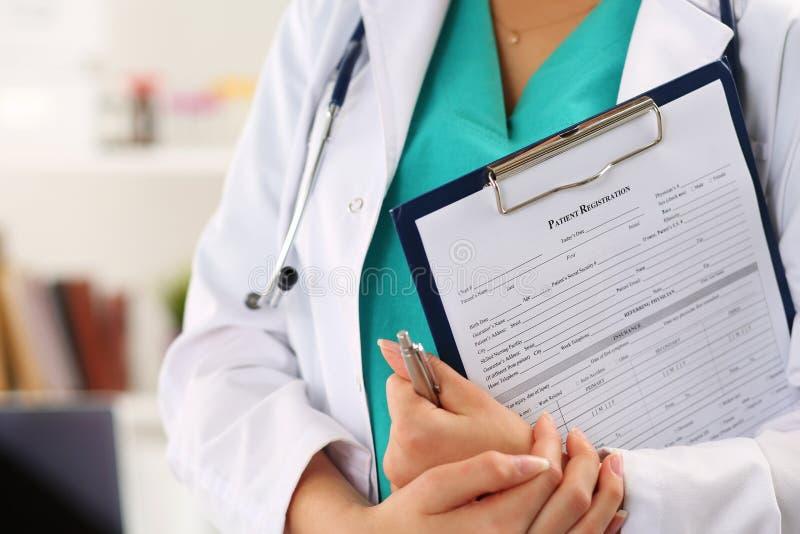 Ciérrese encima de la vista de las manos femeninas del doctor que sostienen registratio paciente imagen de archivo libre de regalías