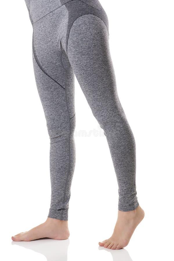 Ciérrese encima de la vista de las piernas de la mujer de la parte delantera en ropa interior termal de los deportes del gris con fotografía de archivo libre de regalías