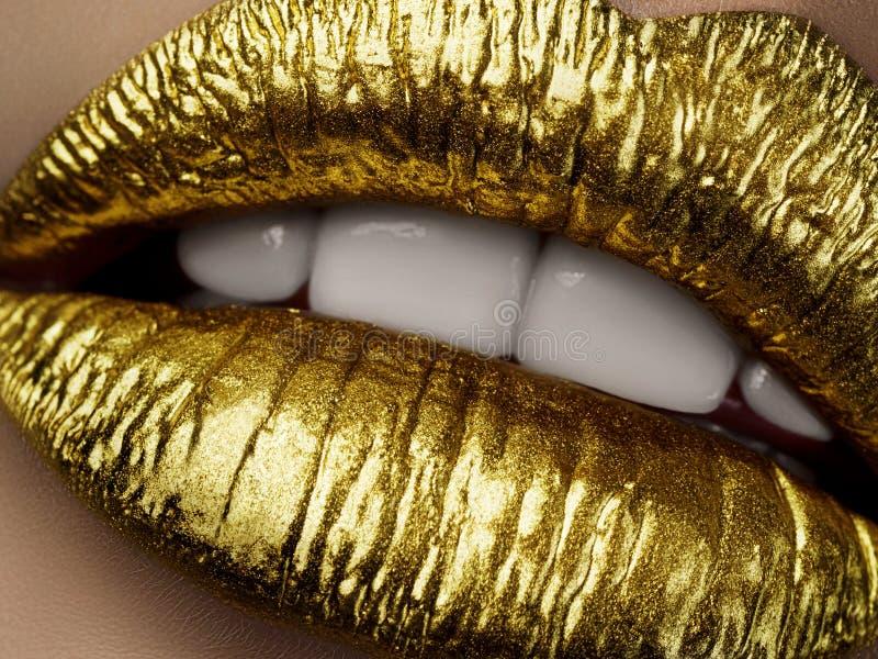 Ciérrese encima de la vista de los labios hermosos de la mujer con el lipst metálico de oro foto de archivo