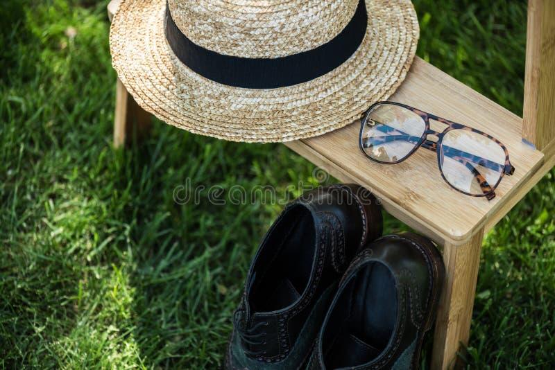 ciérrese encima de la vista del arreglo de lentes, de zapatos negros y del sombrero en las escaleras de madera imagenes de archivo
