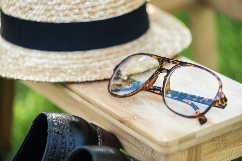 ciérrese encima de la vista del arreglo de lentes, de zapatos negros y del sombrero en las escaleras de madera fotografía de archivo libre de regalías