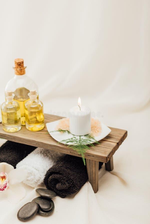 ciérrese encima de la vista del arreglo de los accesorios del tratamiento del balneario con aceite esencial, sal y la vela foto de archivo libre de regalías
