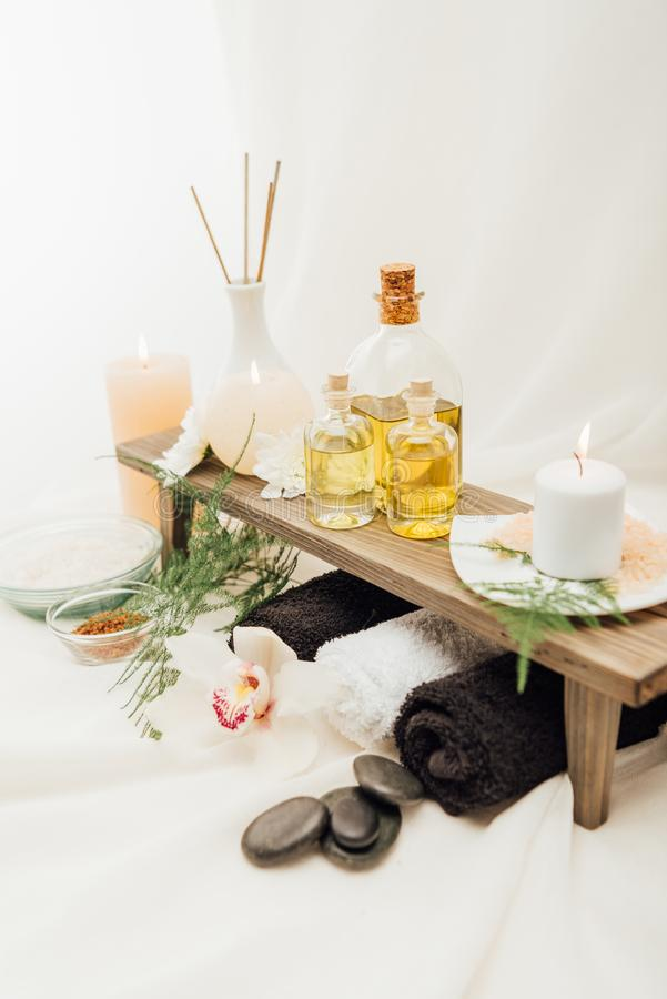 ciérrese encima de la vista del arreglo de los accesorios del tratamiento del balneario con aceite esencial, sal y la vela imagen de archivo