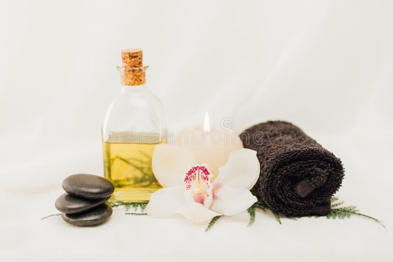 ciérrese encima de la vista del arreglo de los accesorios del tratamiento del balneario con la flor del aceite, de la toalla y de foto de archivo libre de regalías