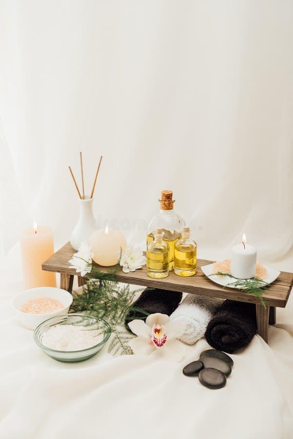ciérrese encima de la vista del arreglo de los accesorios del tratamiento del balneario con las toallas, el aceite y la sal imagen de archivo libre de regalías