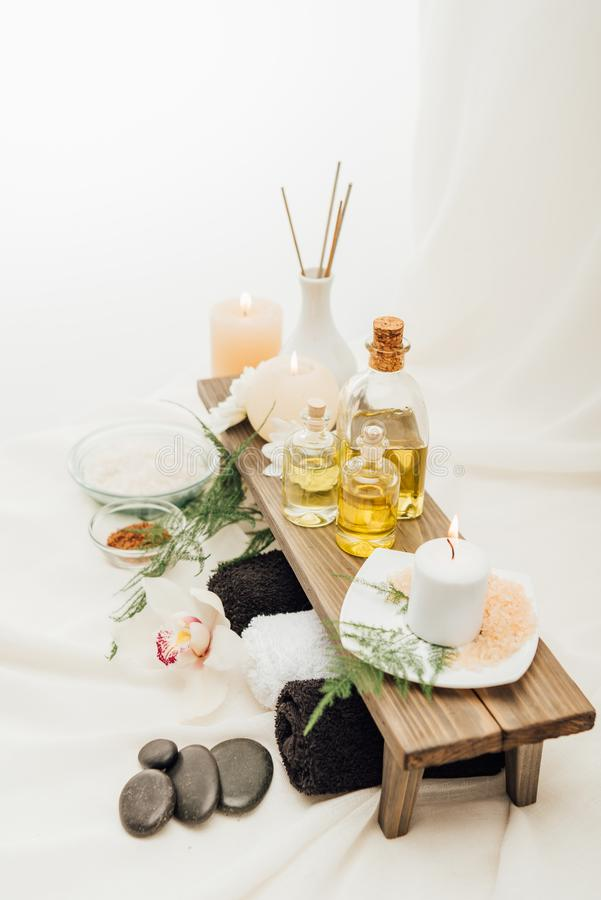ciérrese encima de la vista del arreglo de los accesorios del tratamiento del balneario con las toallas, el aceite y la sal foto de archivo libre de regalías