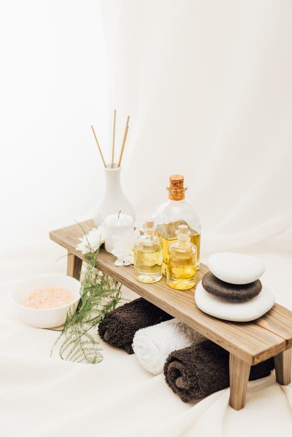 ciérrese encima de la vista del arreglo de los accesorios del tratamiento del balneario con las toallas, el aceite y la sal imágenes de archivo libres de regalías