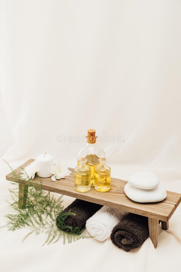 ciérrese encima de la vista del arreglo de los accesorios del tratamiento del balneario con la planta, las toallas, el aceite y l fotos de archivo libres de regalías