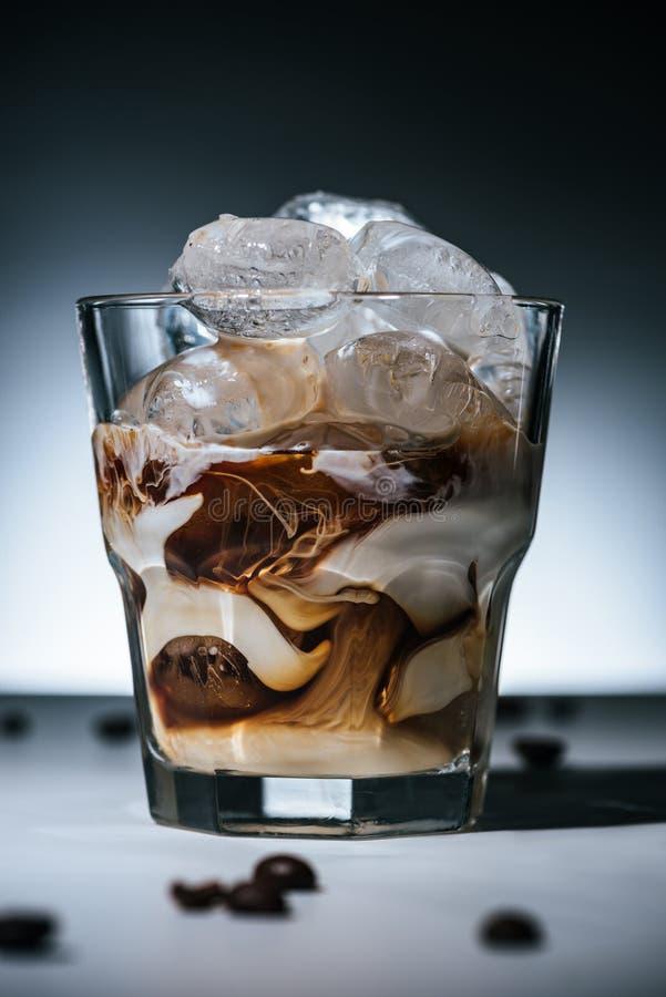 ciérrese encima de la vista del café preparado frío con los cubos de hielo y los granos de café asados en el tablero de la mesa e imagen de archivo