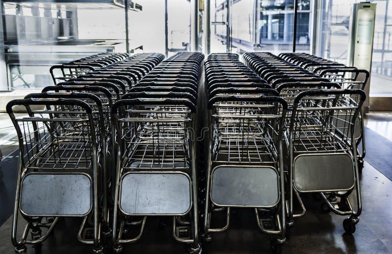 Ciérrese encima de la vista del equipaje de las carretillas en aeropuerto Fila de los carros del equipaje en el aeropuerto fotos de archivo