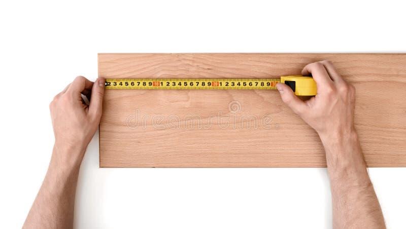 Ciérrese encima de la vista del man& x27; s da el tablón de madera de medición con la línea de la cinta fotos de archivo