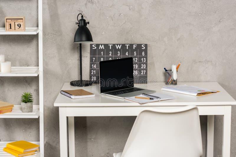 ciérrese encima de la vista del ordenador portátil con la pantalla en blanco, los papeles, el calendario y los cuadernos en el lu fotografía de archivo libre de regalías