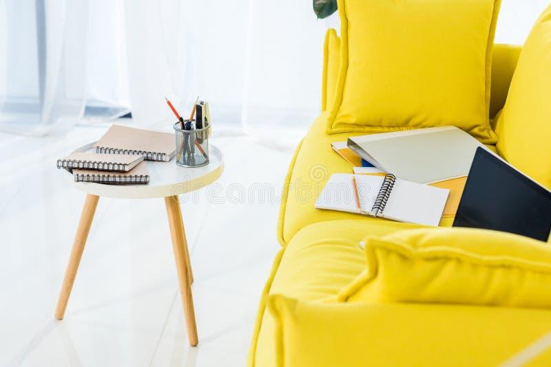 ciérrese encima de la vista del ordenador portátil, de cuadernos y de carpetas en el sofá amarillo foto de archivo