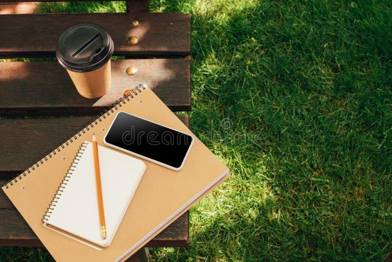 ciérrese encima de la vista del smartphone con la pantalla en blanco, los cuadernos y el café para ir fotos de archivo