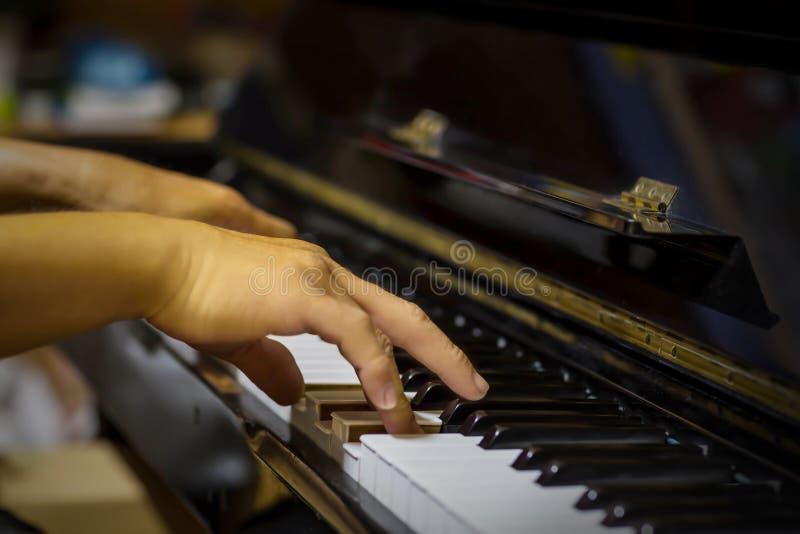 Ciérrese encima de la vista lateral de las manos del hombre que juegan el piano con el fondo borroso imagen de archivo libre de regalías