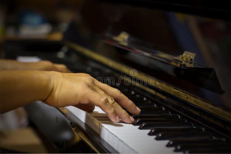 Ciérrese encima de la vista lateral de las manos del hombre que juegan el piano con el fondo borroso fotos de archivo libres de regalías