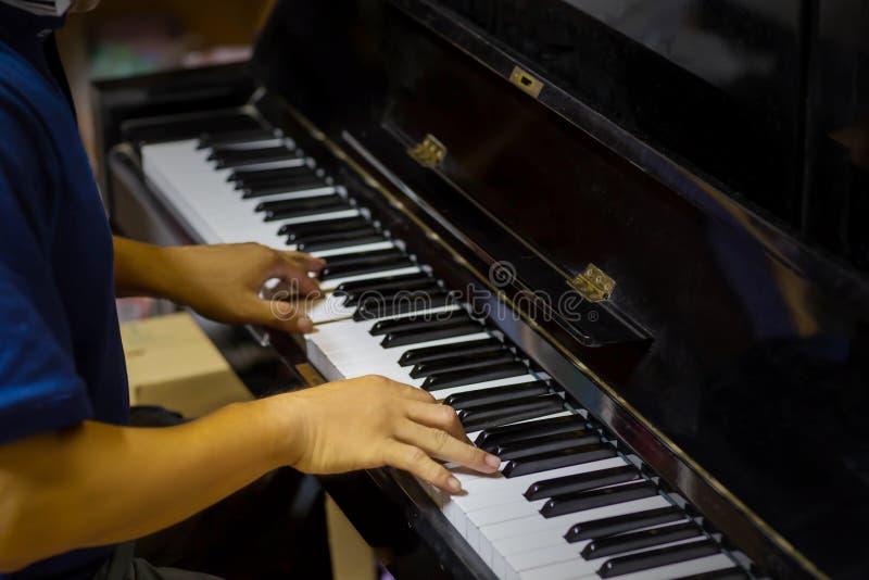 Ciérrese encima de la vista lateral de las manos del hombre que juegan el piano con el fondo borroso imágenes de archivo libres de regalías