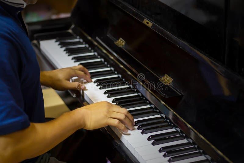Ciérrese encima de la vista lateral de las manos del hombre que juegan el piano con el fondo borroso foto de archivo